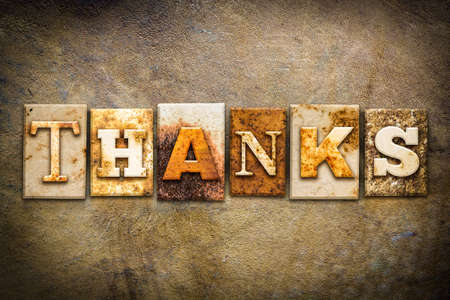 The word THANKS written in rusty metal letterpress type on an old aged leather background.
