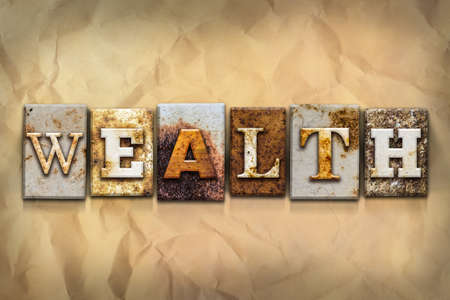 The word WEALTH written in rusty metal letterpress type on a crumbled aged paper background.