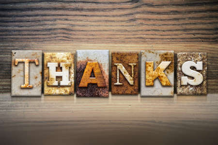 The word THANKS written in rusty metal letterpress type sitting on a wooden ledge background.