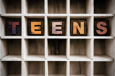 The word TEENS written in vintage ink stained wooden letterpress type in a partitioned printer's drawer.