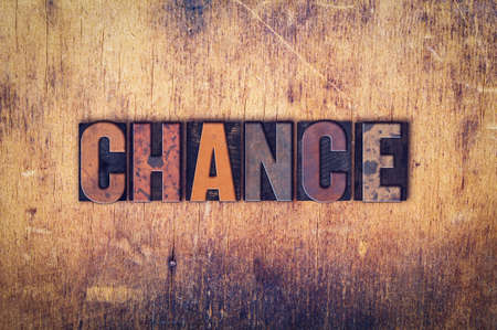 The word Chance written in dirty vintage letterpress type on a aged wooden background.