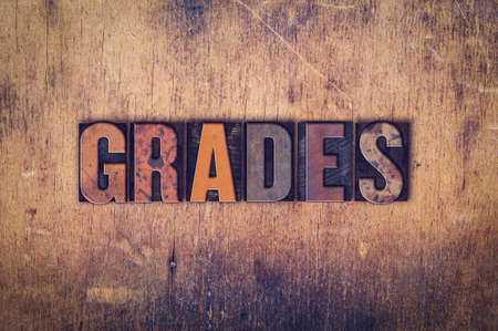 The word Grades written in dirty vintage letterpress type on a aged wooden background.