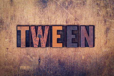 The word Tween written in dirty vintage letterpress type on a aged wooden background.