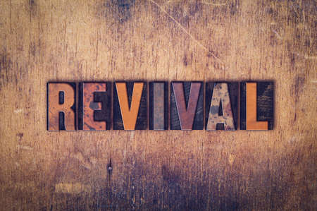 The word Revival written in dirty vintage letterpress type on a aged wooden background.
