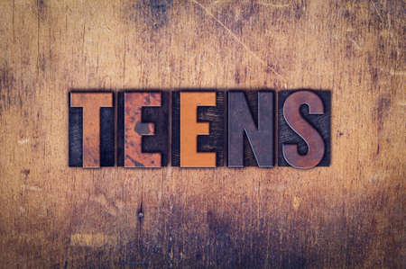 The word Teens written in dirty vintage letterpress type on a aged wooden background.