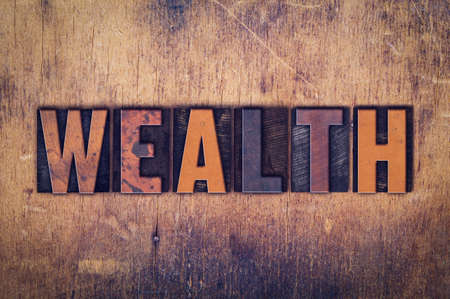 The word Wealth written in dirty vintage letterpress type on a aged wooden background.