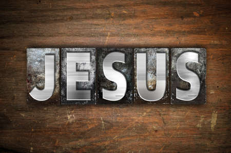 The word Jesus written in vintage metal letterpress type on an aged wooden background.