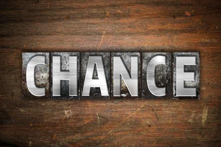 The word Chance written in vintage metal letterpress type on an aged wooden background.