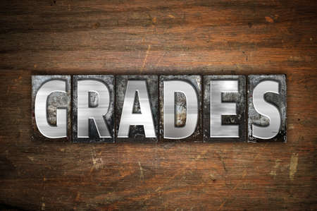 The word Grades written in vintage metal letterpress type on an aged wooden background.