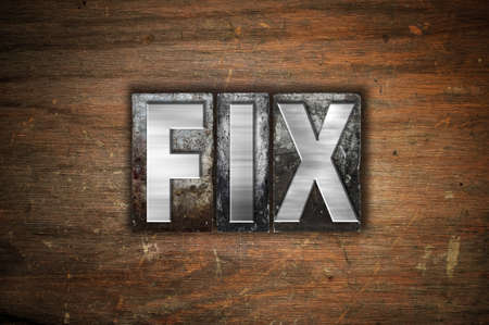 The word Fix written in vintage metal letterpress type on an aged wooden background.