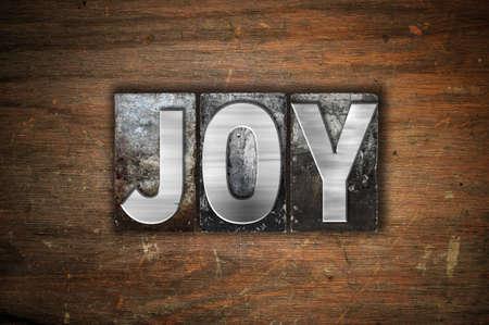 The word Joy written in vintage metal letterpress type on an aged wooden background.