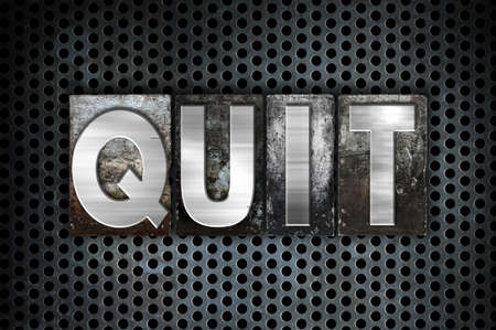 The word Quit written in vintage metal letterpress type on a black industrial grid background.