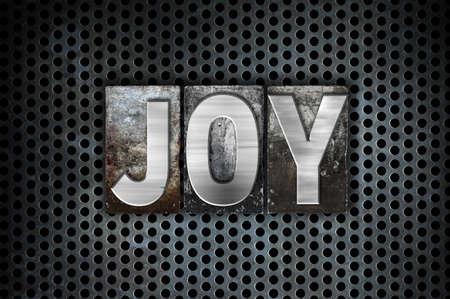 The word Joy written in vintage metal letterpress type on a black industrial grid background.