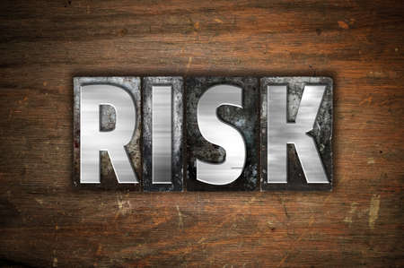 The word Risk written in vintage metal letterpress type on an aged wooden background.