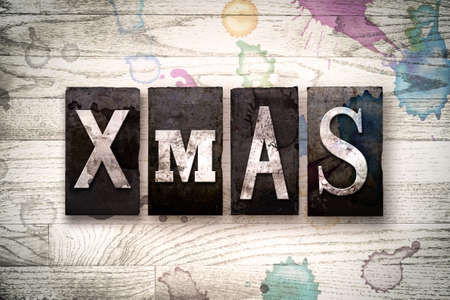 The word XMas written in vintage dirty metal letterpress type on a whitewashed wooden background with ink and paint stains.