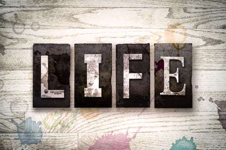 The word LIFE written in vintage dirty metal letterpress type on a whitewashed wooden background with ink and paint stains.