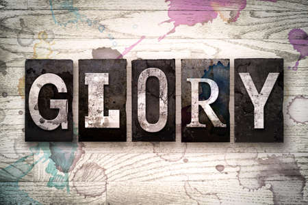 The word GLORY written in vintage dirty metal letterpress type on a whitewashed wooden background with ink and paint stains.
