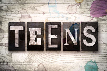 The word TEENS written in vintage dirty metal letterpress type on a whitewashed wooden background with ink and paint stains.