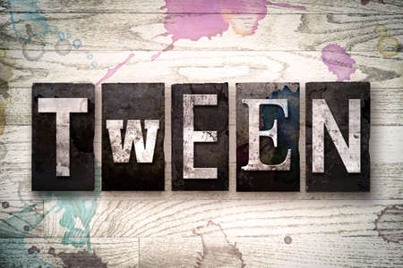 The word TWEEN written in vintage dirty metal letterpress type on a whitewashed wooden background with ink and paint stains.