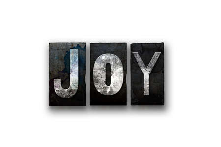 The word JOY written in vintage, dirty, ink stained letterpress type and isolated on a white background.