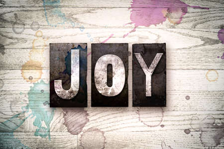 The word JOY written in vintage, dirty metal letterpress type on a whitewashed wooden background with ink and paint stains.