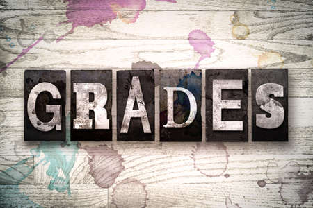 The word GRADES written in vintage, dirty metal letterpress type on a whitewashed wooden background with ink and paint stains.