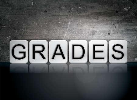 The word Grades written in white tiles against a dark vintage grunge background.