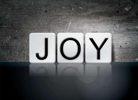 The word Joy written in white tiles against a dark vintage grunge background.