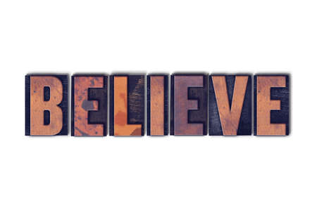 The word Believe concept and theme written in vintage wooden letterpress type on a white background.