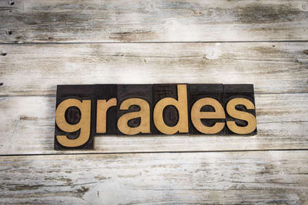 The word grades written in wooden letterpress type on a white washed old wooden boards background.