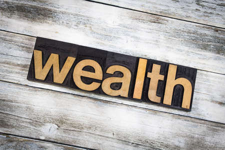 The word wealth written in wooden letterpress type on a white washed old wooden boards background.