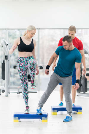 instructor trainer showing how to do exercise with a group of people in the gym