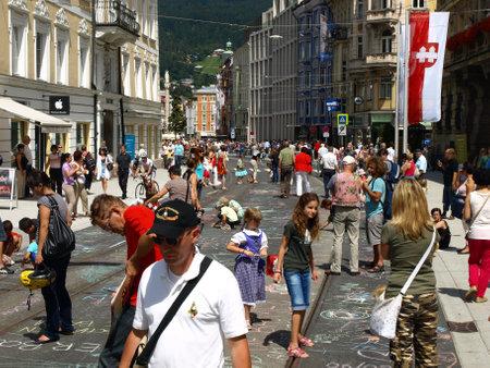 Foto per Innsbruck, Austria - 6 agosto 2011 - Le vie della città aperte ai bambini che liberano la loro fantasia colorando vivacemente con  i gessetti  le strade principali. - Immagine Royalty Free