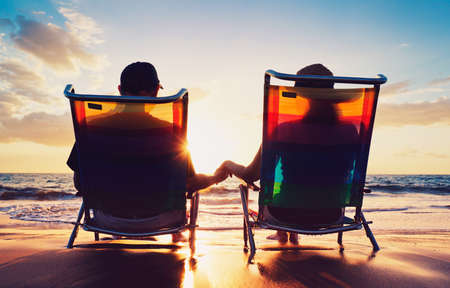 Foto de senior couple of old man and woman sitting on the beach watching sunset - Imagen libre de derechos