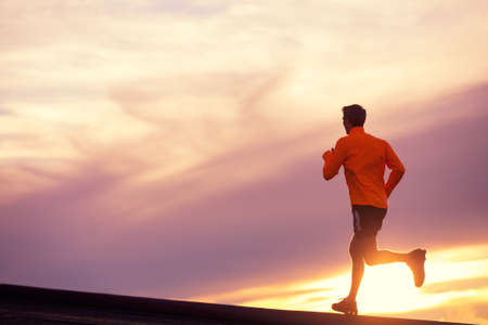 Photo pour Male runner silhouette, Man running into sunset, colorful sunset sky  - image libre de droit