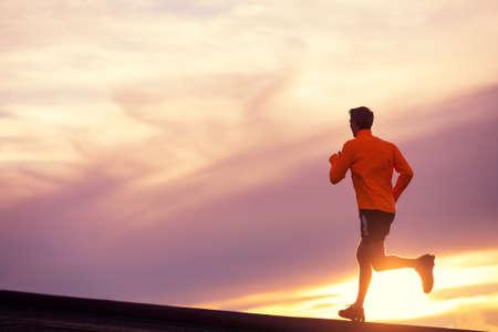 Foto de Male runner silhouette, Man running into sunset, colorful sunset sky  - Imagen libre de derechos