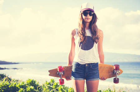 Beautiful hipster girl with skate board wearing sunglassesの写真素材