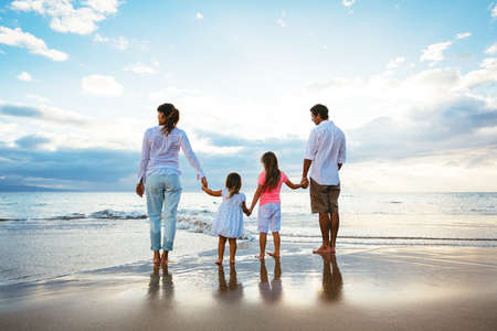 Foto de Happy young family watching the sunset at the beach.  Happy Family Lifestyle  - Imagen libre de derechos