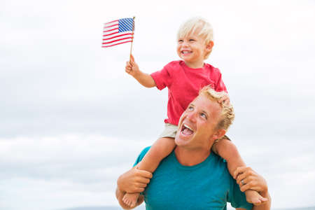 Photo pour Father and son playing on the beach with American flag. USA celebrate 4th of July. - image libre de droit