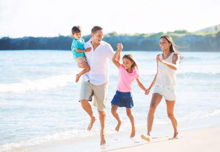 Foto de Happy Mixed Race Family of Four Playing on the Beach - Imagen libre de derechos