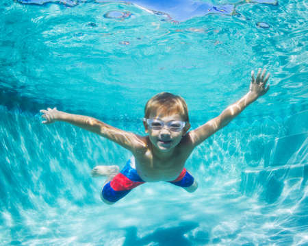 Underwater Young Boy Fun in the Swimming Pool with Goggles. Summer Vacation Fun.