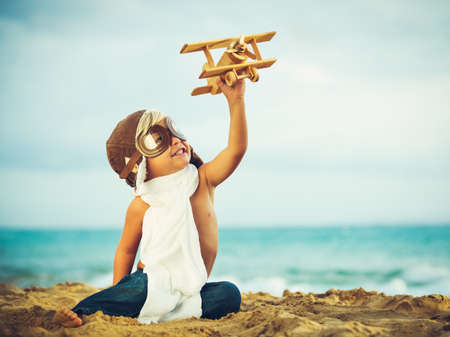 Photo pour Small Boy Playing with Toy Airplane - image libre de droit