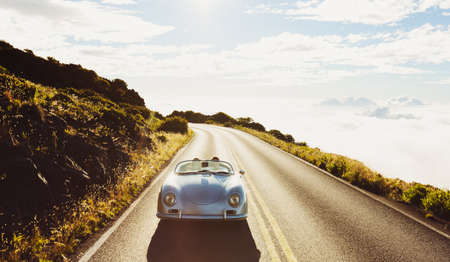 Photo for Happy Couple Driving on Country Road in Classic Vintage Sports Car - Royalty Free Image