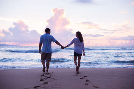 Young Lovers Walking on the Beach at Sunset on Tropical Vacation