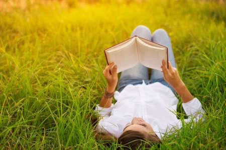 Photo pour Young Woman Enjoying a Book Reading Outdoors - image libre de droit