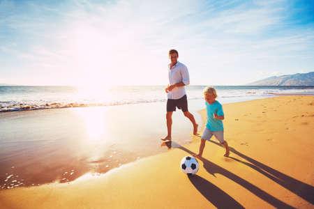 Foto de Happy Father and Son Having Fun Playing Soccer on the Beach at Sunset - Imagen libre de derechos