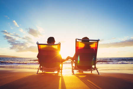 Retirement Vacation Concept, Happy Mature Retired Couple Enjoying Beautiful Sunset at the Beachの写真素材