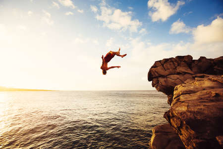 Photo pour Cliff Jumping into the Ocean at Sunset, Outdoor Adventure Lifestyle - image libre de droit