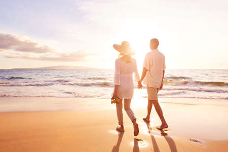 Happy Romantic Middle Aged Couple Enjoying Beautiful Sunset Walk on the Beach. Travel Vacation Retirement Lifestyle Conceptの写真素材