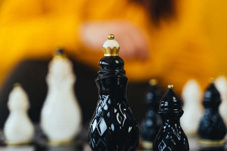 Photo pour Selective focus of beautiful chess on chessboard in room. Close up of body part of unrecognizable woman playing in board game - image libre de droit